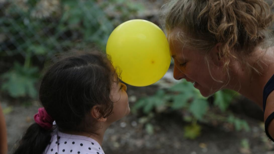 On a spring break community service trip in Costa Rica, a student and child play an Early Childhood Development game using a balloon.